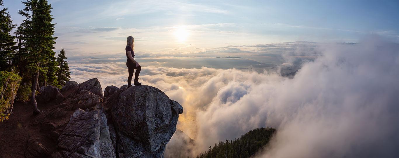Gipfelstrategie - Frau steht auf einem Gipfel und schaut die Kippe hinab