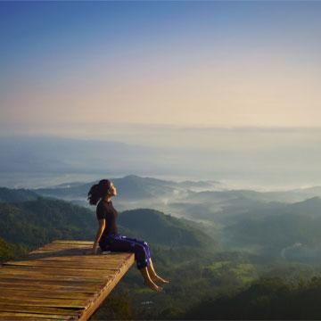 Gipfelstrategie - Frau sitzt an einer Klippe