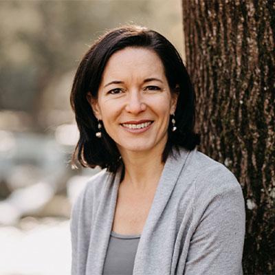 Karin Maria Pflügler angelehnt an einen Baum